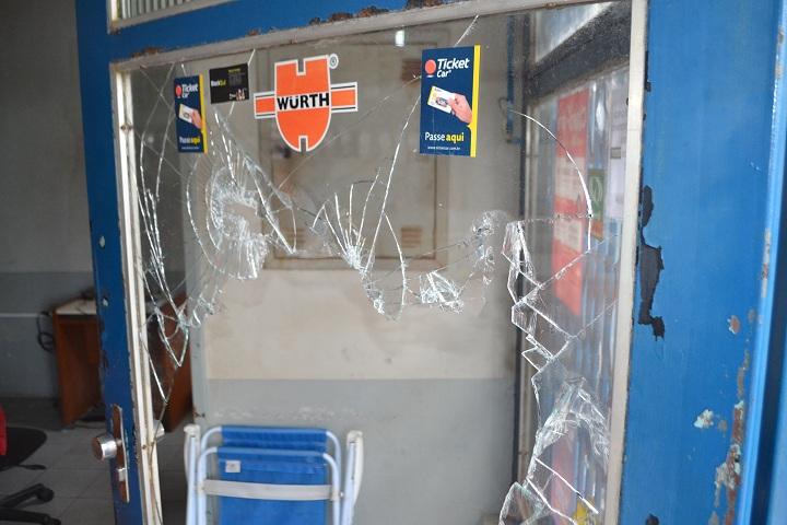 O vidro da porta da frente do escritório do posto de combustíveis foi quebrado
