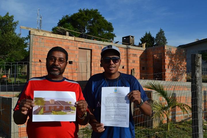 Valtair e o filho Jonata exibem o contrato do terreno e o projeto da nova casa que a família já está construindo