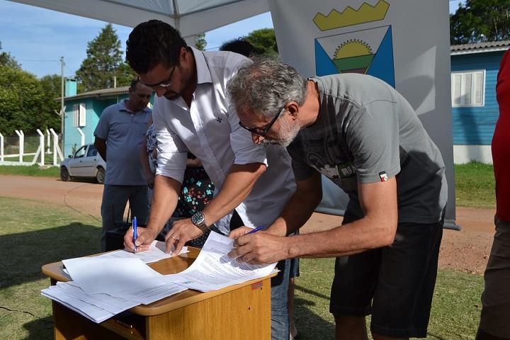Prefeito Adriano e o morador Leonel de Figueiredo assinam o contrato